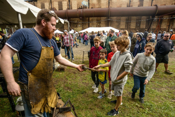 blacksmith shows his hammer to a group of boys