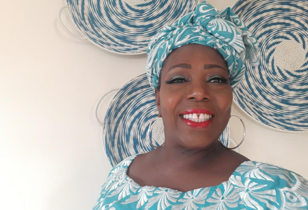 A smiling black woman dressed in a beautiful blue and white print with a matching headwrap with blue and white traditional baskets in the background.