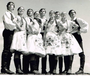 Black and white photo of 10 dancers, men and women, in traditional Eastern European dress.