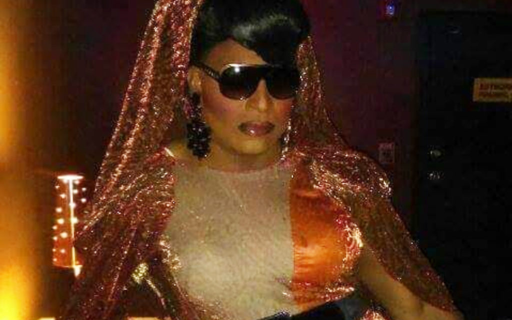 A Black drag queen wearing sunglasses in a dark room.