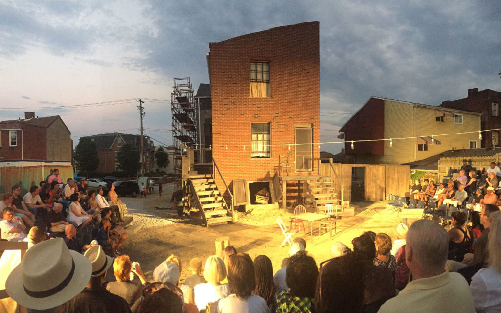 A crowd of theater-goers sitting in the round behind the August Wilson House.